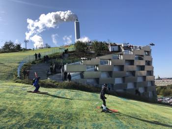 Auf grünen Matten führt die Piste vom Dach des Gebäudes hinunter ins Tal.