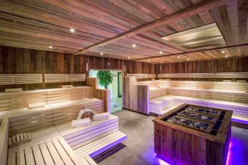 In der Panoramasauna sorgen stimmungsvolle Beleuchtung und moderne Holztöne für echte Entspannungsmomente