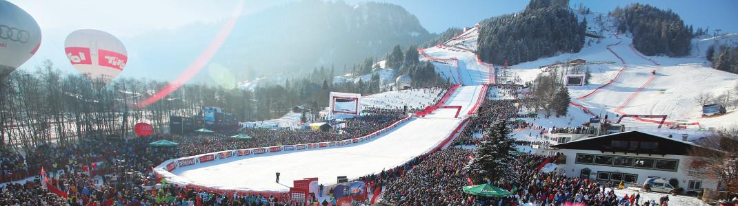 Von einer jubelnden Menge werden die Abfahrtsläufer im Zielgelände erwartet. Rechts oben sind auch Teile des Ganslernhangs zu sehen, auf dem sich die Slalomläufer am Sonntag messen.