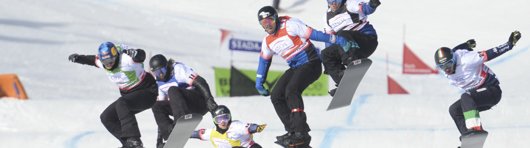 Im direkten Duell fahren die Snowboarder auf der Cross-Strecke um den Sieg.