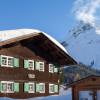 Die Pension Sandbur - das Walserhaus - gehört zum historischen Ensemble im Ortskern von Lech am Arlberg, zusammen mit der Dorfkirche, der alten Schule, dem alten Gericht und dem Messmer Stall. Im Hintergrund das Omeshorn.