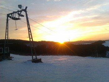 Die Sonne geht unter über dem Sauerland. Durch die Flutlichtbeleuchtung ist Skifahren am Grevenstein Skilift jedoch auch abends möglich.