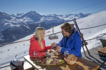 Zur Mittagspause gibt es eine Bünderplatte auf der Alpina Hütte mit Blick auf die FIS-Piste und die Luftseilbahn Piz Nair.
