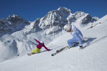 Sowohl Snowboarder als auch Skifahrer finden im Skigebiet Corviglia ihre Lieblingspisten. Hier zwei Wintersportler bei der Abfahrt mit dem Piz Albana und dem Piz Julier im Hintergrund.