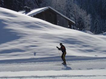 Die Loipe führt an traditionellen Häusern im Schweizer Ort Champéry vorbei.